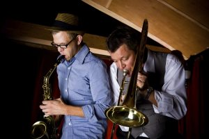 Two hipsters musicians play jazz in a dimly lit restaurant. One has a sax and one has a trombone.